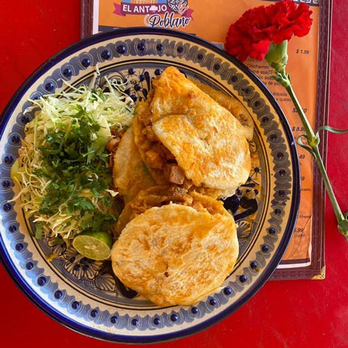 full plate of gorditas rellenas plated on red table with rose