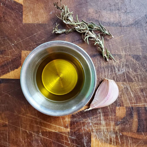 olive oil with garlic clove and fresh rosemary