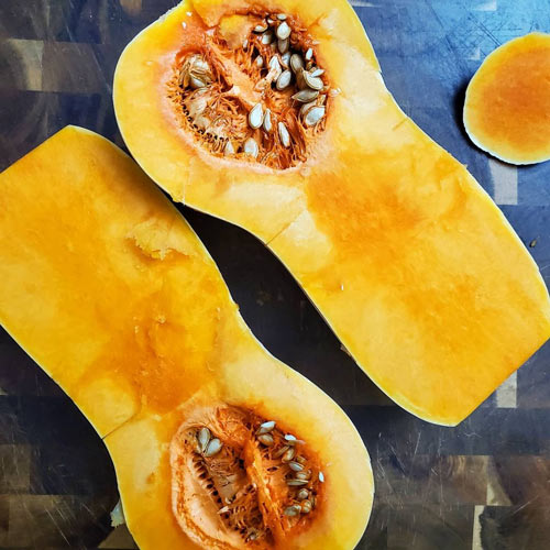 openly halved butternut squash on cutting board
